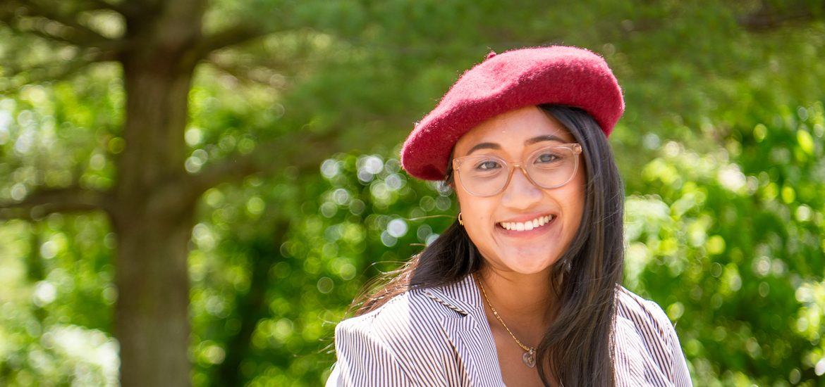 Stephanie wears glasses and a red beret smiling at the camera with a green forest in the background.