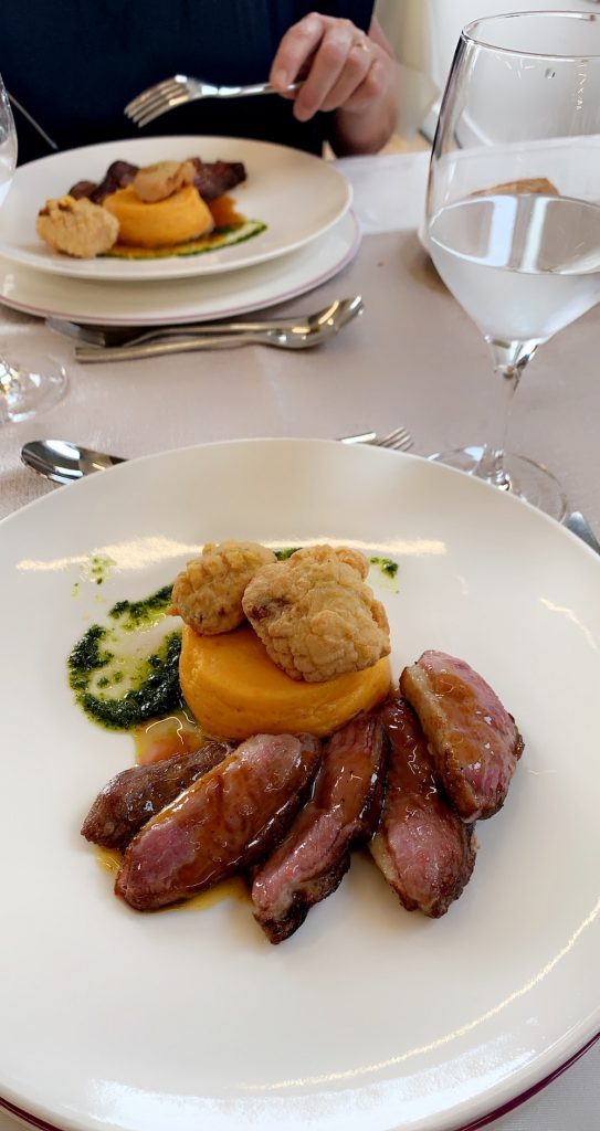 Fancy French food on a white plate prepared by a culinary student in France.