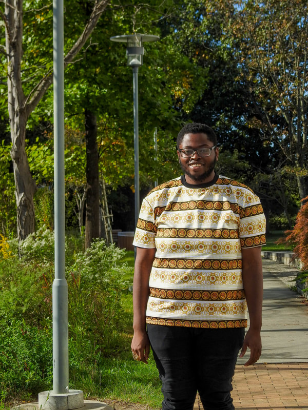 Denzell smiling and posing for a photo outside the engineering trail.