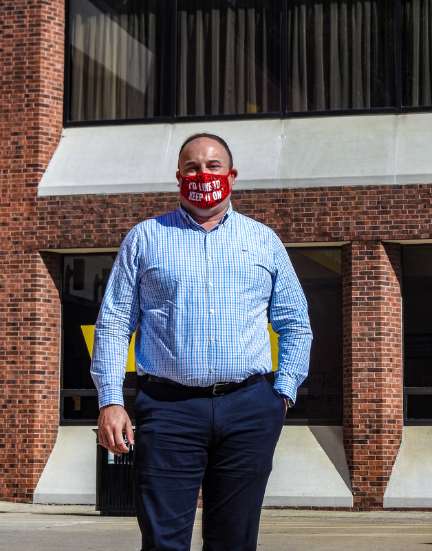 Drew posing outside the Chamberlain Student Center with a red mask on.