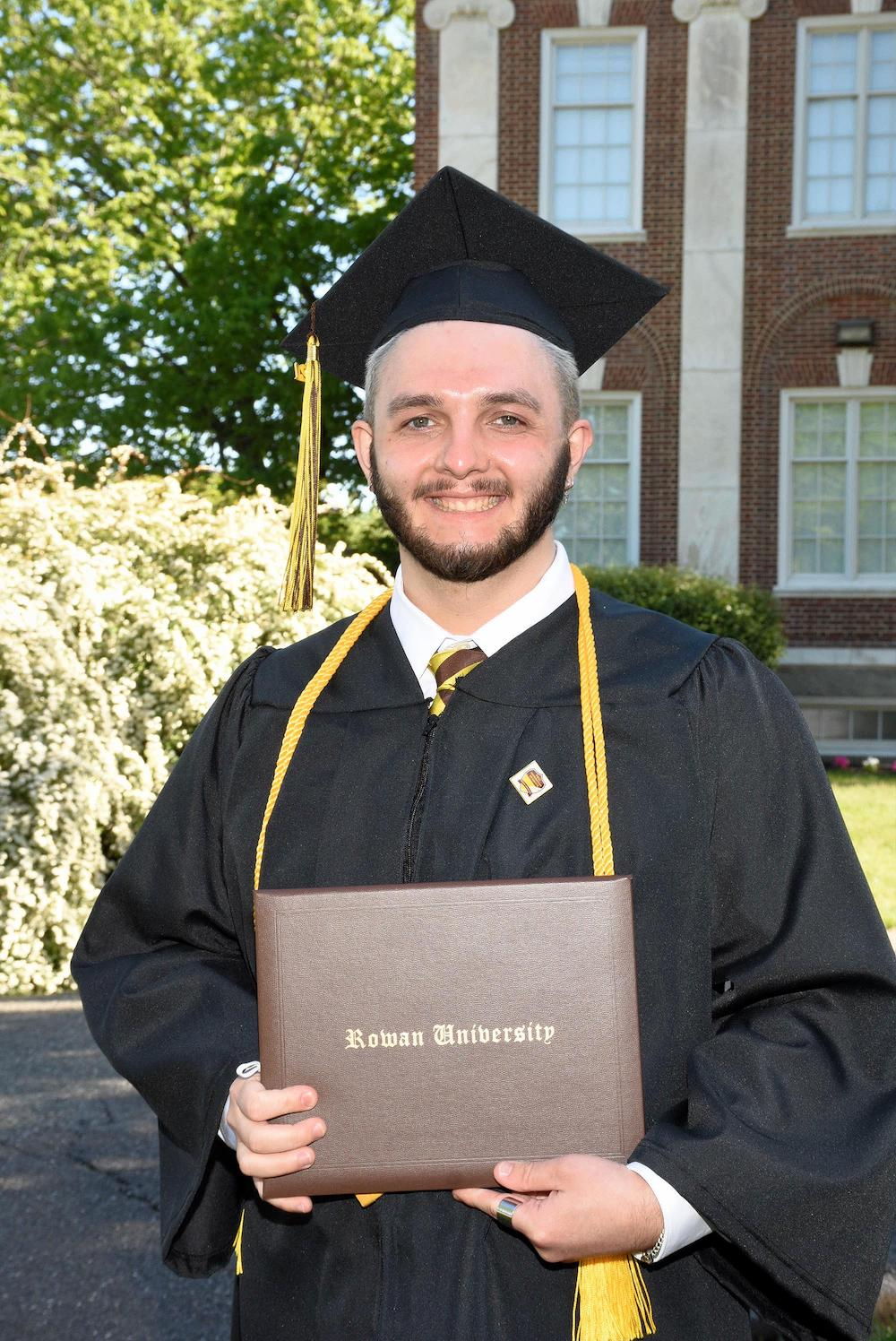 Scott holds his diploma at commencement.