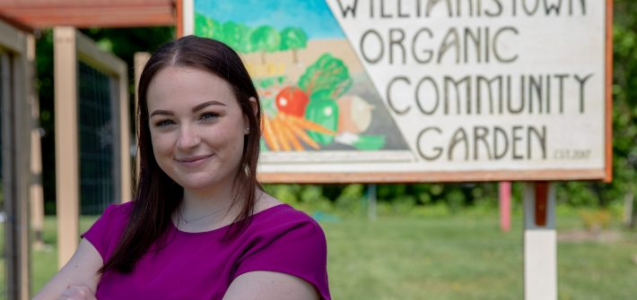 Jenna stands by the entrance sign for the Williamstown Organic Community Garden.