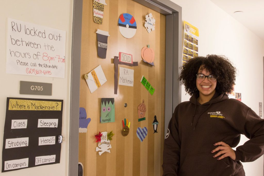 An RA stands next to her door.