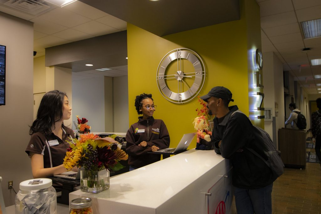 A student asks for help at the Information Desk on the main level of the Student Center.
