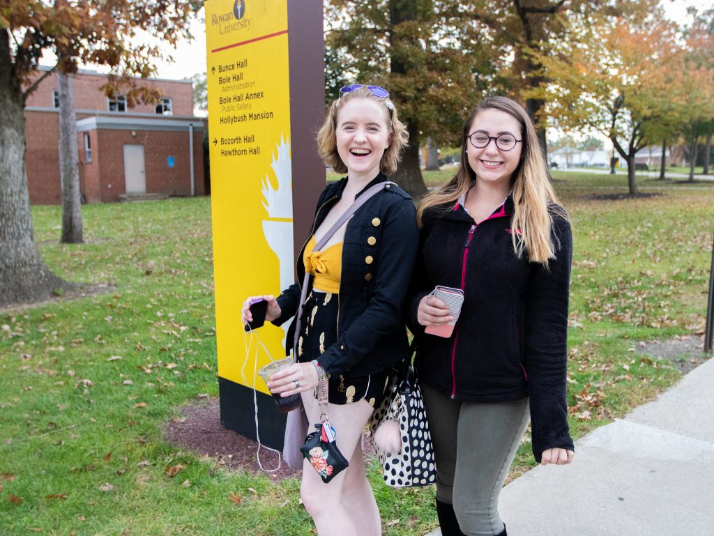 Two girls pose in front of a sign that gives directions.