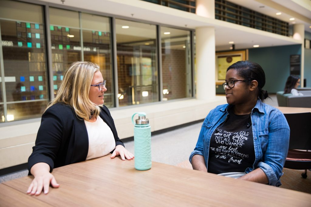 An instructor speaks with a student inside James Hall.