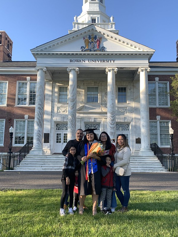 A graduate poses with her family in front of Bunce Hall.