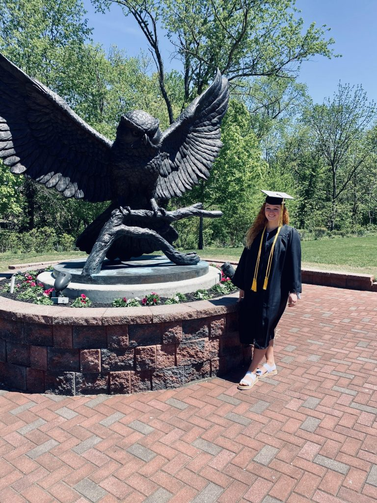 Chloe stands in front of the Owl Statue