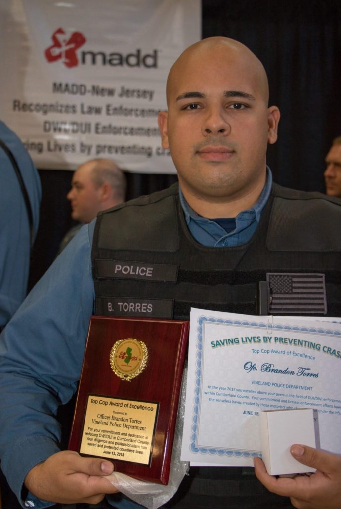 Brandon holding a plaque for Top Cop  Award of Excellence.
