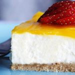Close up of a slice of white cheesecake with lemon yellow glaze and a strawberry.