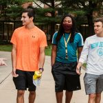Five students walk and talk on campus.
