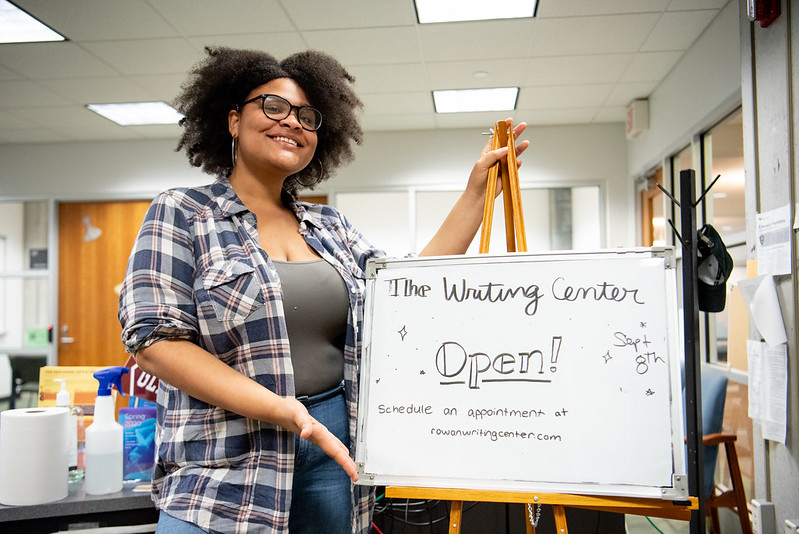 Bianca stands next to a sign in The Writing Center.