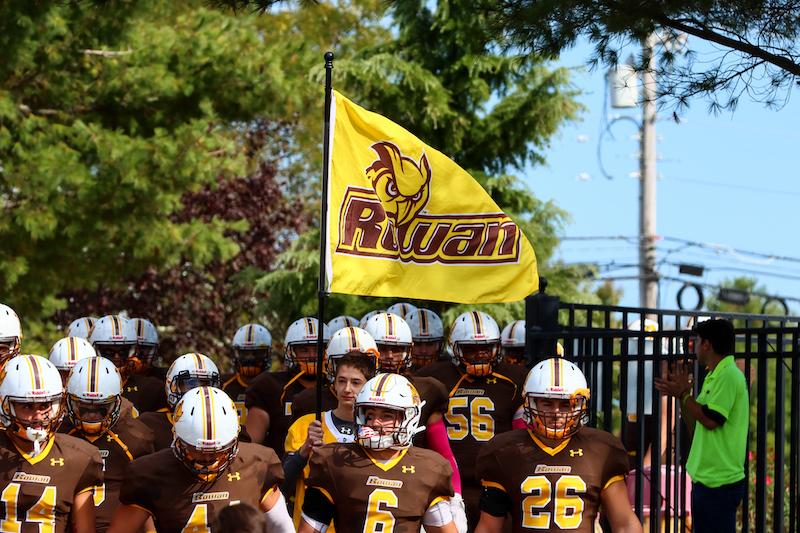 Rowan's football team enters the stadium.
