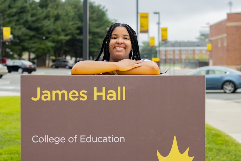 London leans against a sign of James Hall.