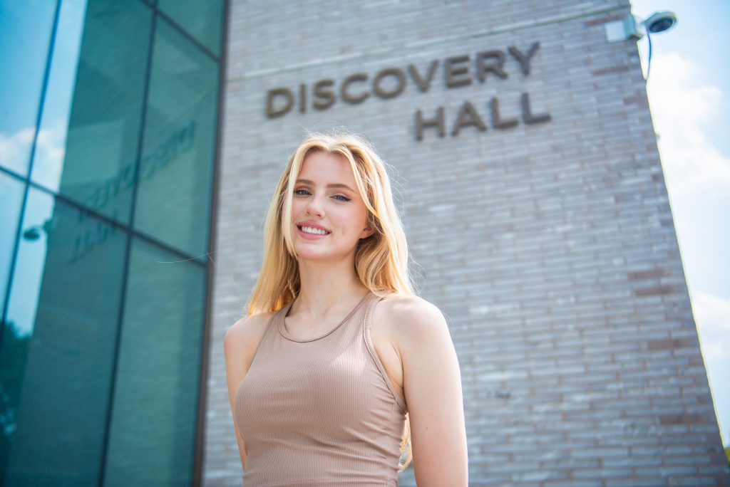 Lauren smiles and stands in front of Discovery Hall.