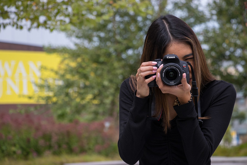 Student holds a DSLR camera in front of Wilson Hall.
