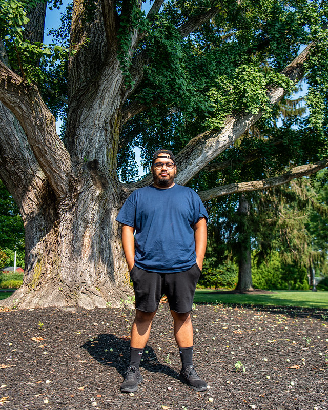 Alex stands in front of a large tree on Bunce Green.