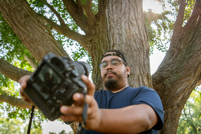 Alex takes a selfie with his DSLR camera.