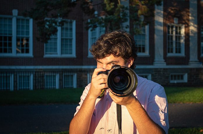 Nick holds a DSLR camera in front of Bunce Hall.