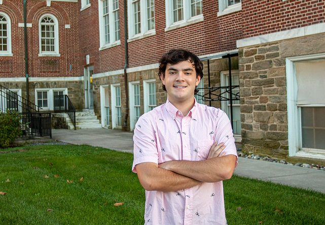 Nick stands on the side of Bunce Hall.