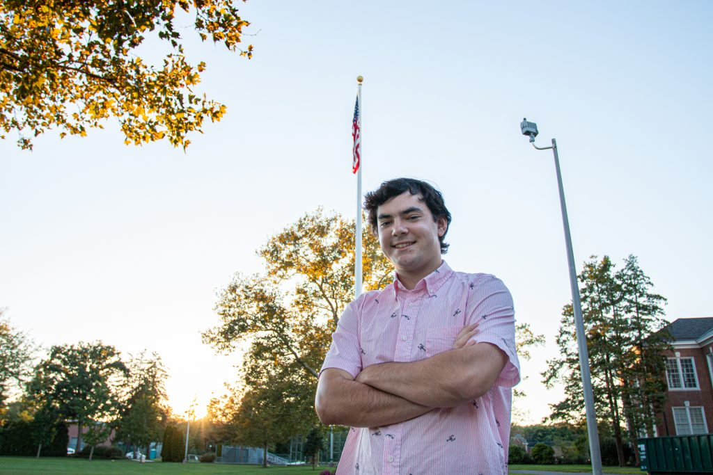 Nick poses in front of a tree and the American flag.