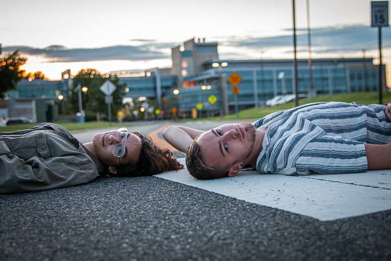 Artsy photo of two students laying down on a road, head to head, with the engineering building behind them.