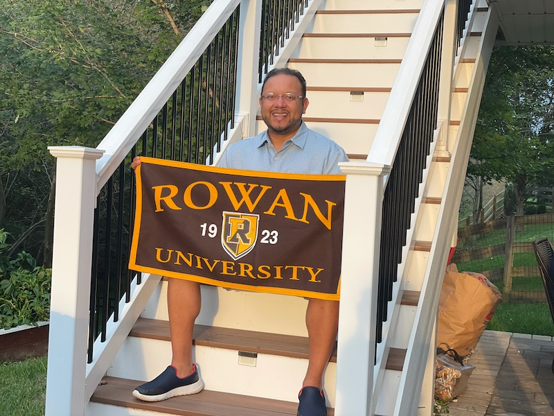 Byron holds a Rowan flag while sitting on a flight of stairs.